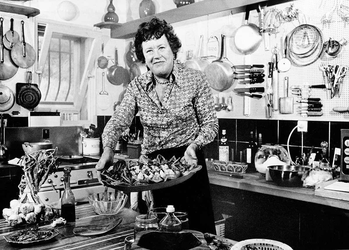 FILE- In this Aug. 21, 1978 file photo shows American television chef Julia Child showing a salade nicoise she prepared in the kitchen of her vacation home in Grasse, southern France. More so than the tools and techniques she popularized, Child's most lasting legacy may be her spirit and sense of humor. That was the conclusion of several chefs and food magazine editors asked to describe Child's memorable contributions to American home cooking as a new movie about her life is about to open. (AP Photo)